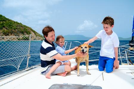 호화스러운 요트 또는 뗏목 보트에 아버지, 아이들과 그들의 애완 동물 개 항해