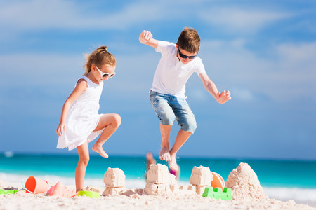 sandcastle: Two kids crushing sandcastle on summer vacation