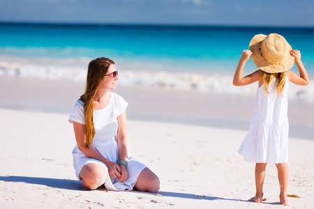 Young mother and her adorable little daughter on summer beach vacation photo