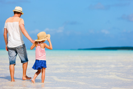 Father and daughter at deserted tropical beach photo