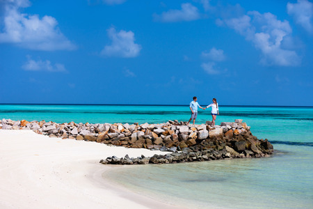 Young beautiful couple walking at tropical beach on exotic island Stock Photo - 30963526