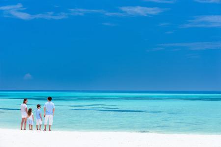 여름 휴가를 즐기는 4 인 가족와 아름 다운 열 대 해변 풍경