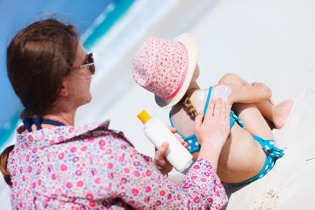 Mor applicerar solskyddskräm på hennes döttrar axel
