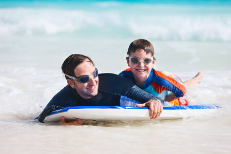 Father and son on vacation having fun surfing on boogie board photo