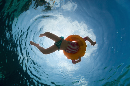 under water: Underwater photo of a little girl swimming with inflatable ring in pool Stock Photo