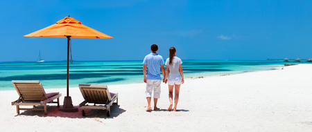 Back view of a couple on a tropical beach vacation panorama perfect for banners photo
