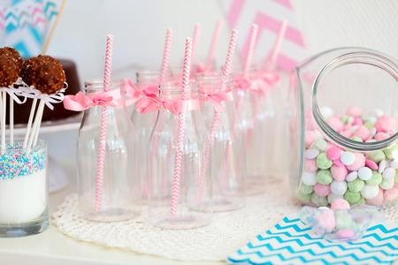 파티 또는 결혼식 축하에 디저트 테이블에 음료 사탕 항아리와 멋진 우유 병 스톡 콘텐츠