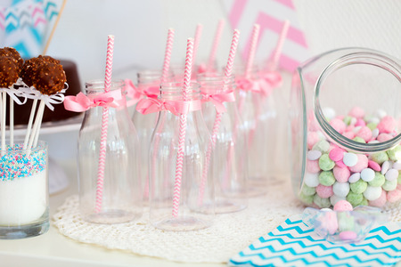 milk bottle: Candy jar and fancy milk bottles for drinks on a dessert table at party or wedding celebration