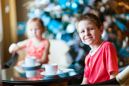 cofffee: Two children drink tea from white cups in a room decorated for Christmas Stock Photo