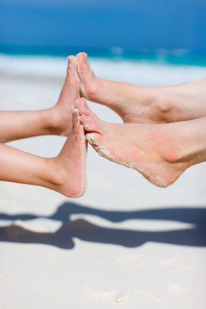feet in sand: Close up of mother and daughter feet on a tropical sandy beach during vacation Stock Photo