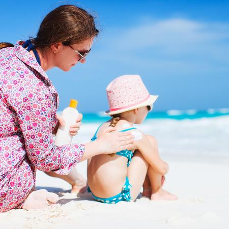 어머니는 그녀의 딸의 어깨에 썬 블록 크림을 적용
