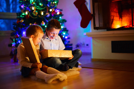 fireplace christmas: Little kids opening presents next to the tree and fireplace in a cozy home celebrating Christmas