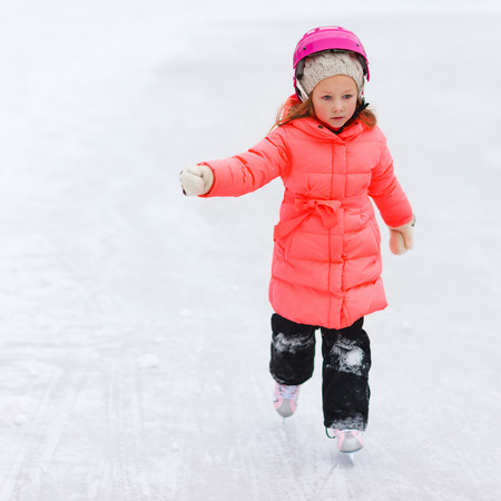 figure skating: Adorable little girl outdoors on beautiful winter day ice skating Stock Photo