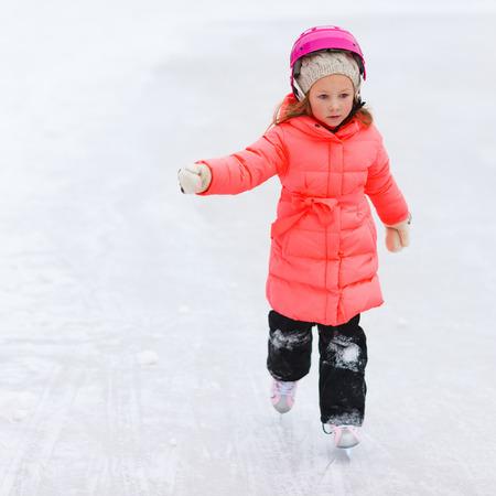 patinaje sobre hielo: Adorables pequeños al aire libre niña en invierno hermoso día de patinaje sobre hielo Foto de archivo