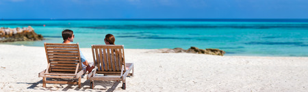 Back view of a couple relaxing on a tropical beach during summer vacation, panorama perfect for banners photo