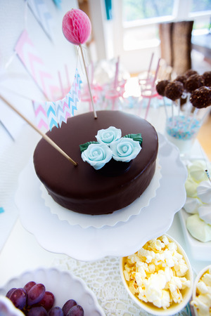 Wide angle photo of delicious chocolate cake with blue sugar flower photo