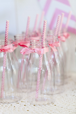 Milk bottles for drinks on a dessert table at party or wedding celebration photo