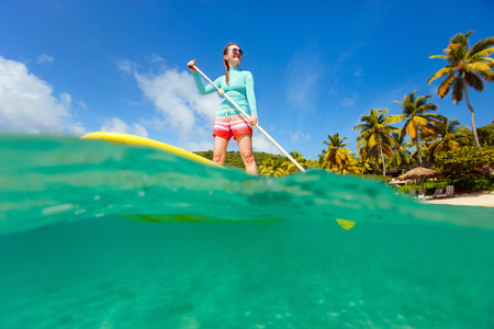 paddling: Split underwater photo of young sporty woman on tropical beach vacation paddling on stand up board Stock Photo