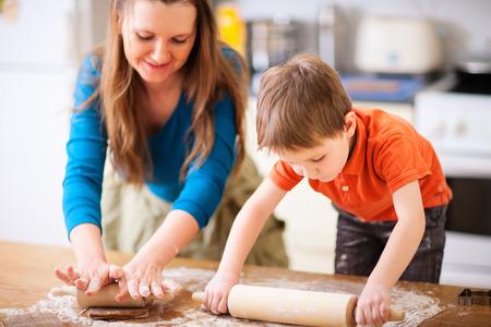 niños cocinando: Joven madre y su pequeño hijo para hornear galletas juntos en la cocina en casa