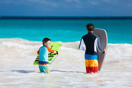 bodyboard: Father and son running towards ocean with boogie boards having fun on beach vacation
