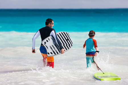 boogie: Father and son running towards ocean with boogie boards having fun on beach vacation
