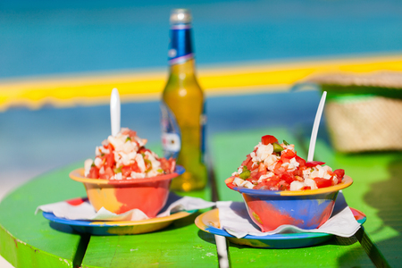 bahamian: Two bowls of Bahamian conch salad and bottle of beer Stock Photo