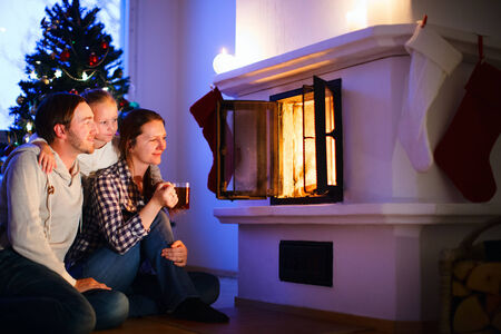 Family sitting by a fireplace in their family home on Christmas eve photo