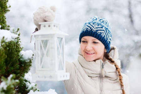 Young woman holding Christmas lantern outdoors on beautiful winter snow day photo