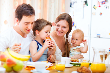 baby eating: Young happy family with two kids having breakfast together at home