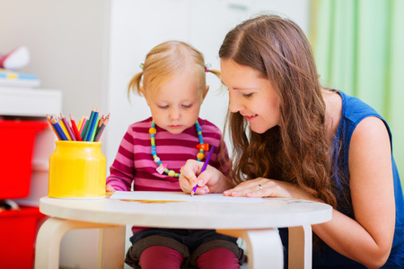 Young mother and her little daughter drawing together photo