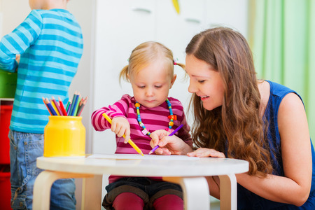 Young mother and her daughter drawing together. Also perfect for kindergarten daycare context. Stockfoto