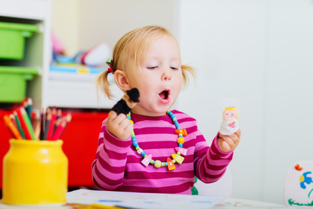 Adorable toddler girl playing with finger puppets at home or daycare photo