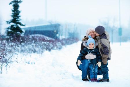 ropa de invierno: Joven madre con dos niños al aire libre en el hermoso día de invierno con nieve