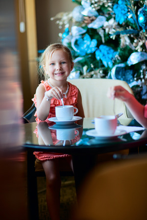 cofffee: Little girl drinking tea from a white cup in a room decorated for Christmas Stock Photo