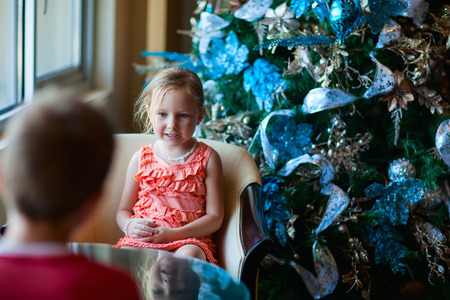 cofffee: Two children drinking tea from white cups in a room decorated for Christmas Stock Photo