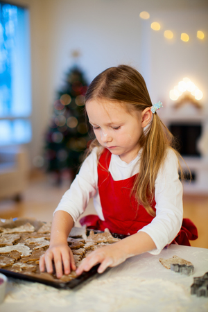 Little girl baking Christmas cookies at home photo