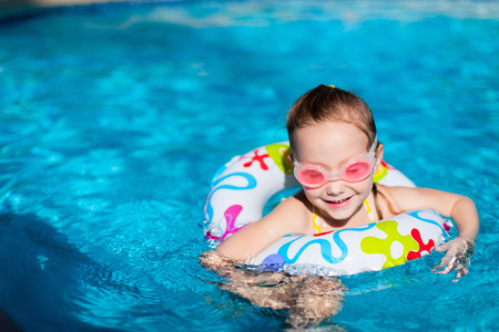 Adorable little girl at swimming pool having fun during summer vacation photo