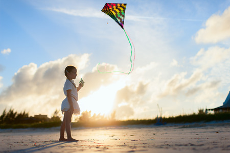 flying a kite: Little girl having fun flying a kite at beach during sunset