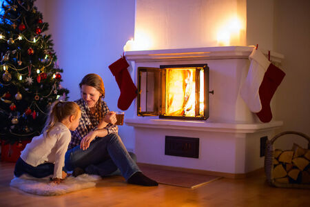 Mother and daughter sitting by a fireplace in their family home on Christmas eve photo