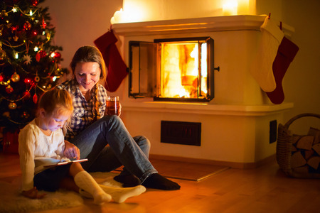 Mother and daughter sitting by a fireplace in their family home on winter photo
