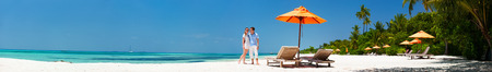 Romantic couple on a tropical beach during honeymoon vacation, super wide panorama perfect for banners