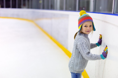 Adorable little girl wearing jeans, warm sweater and colorful hat skating on ice rink Foto de archivo