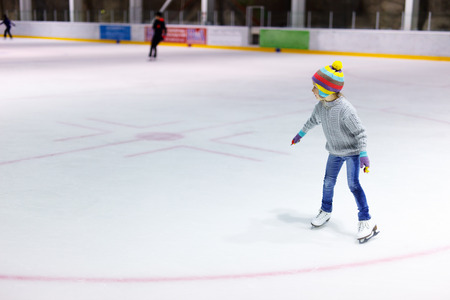 Adorable little girl wearing jeans, warm sweater and colorful hat skating on ice rink Archivio Fotografico