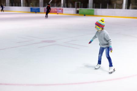 Petite fille portant des jeans adorable, chandail chaud et chapeau coloré patinage sur la patinoire