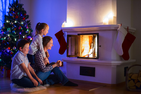 Mother and her two little kids sitting by a fireplace in their family home on Christmas eve photo