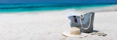 Strooien hoed, tas, zonnebril en slippers op een tropisch strand Stockfoto
