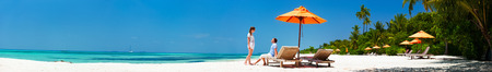 panoramic: Romantic couple on a tropical beach during honeymoon vacation Stock Photo