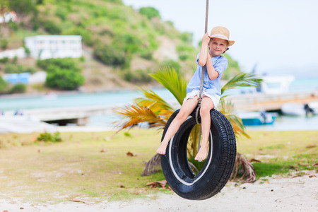 Adorable little girl having fun on tire swing on summer day Stock Photo