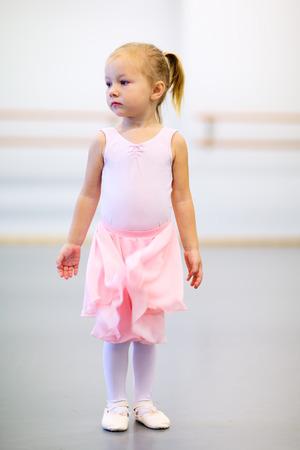 Adorable little ballerina wearing pink leotard in a dancing school photo