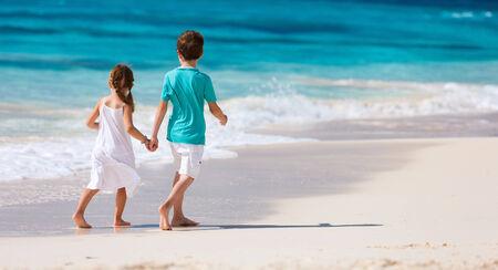 Brother and sister walking along a beach at Caribbean photo